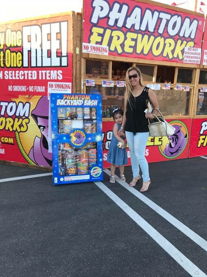 two people infront of a phantom fireworks stand with fireworks